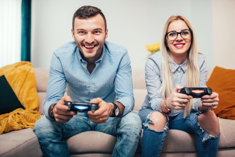 Gift par som spelar videospel på den allmänna dobbelkonsolen Detaljer av den moderna livsstilen med par som har gyckel arkivbilder