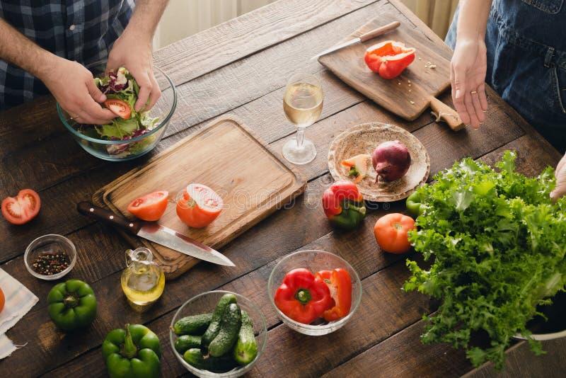 Gift par som tillsammans lagar mat matställegrönsaksallad matlagning royaltyfria foton