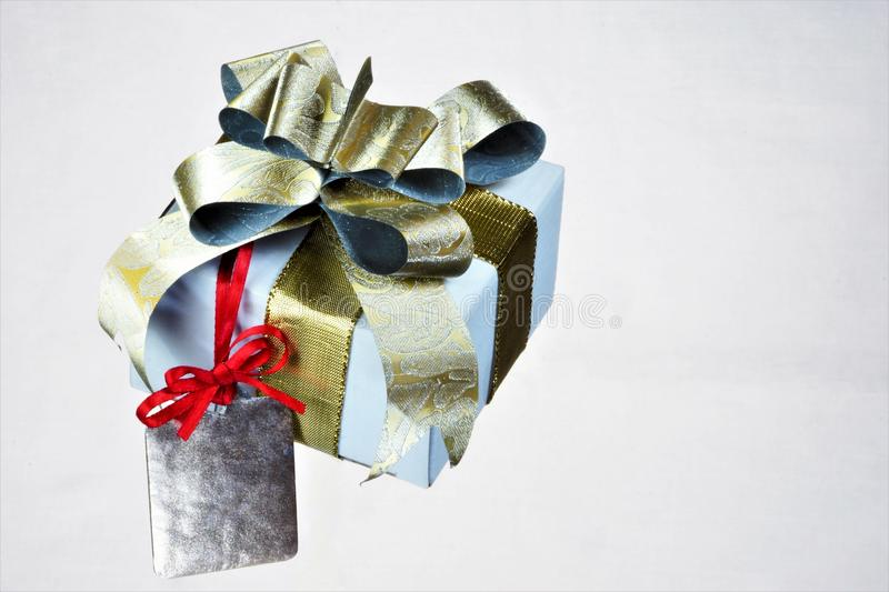 Gift parcel with bow, gold ribbon, tag label, white background, red bow. Label frame indicating important text, picture, price, stock image