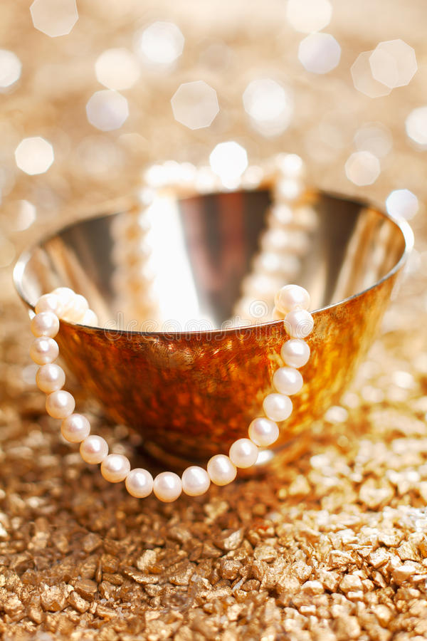 A Gift Of Pearls. A matched string of pearls cascades down from a pretty silver bowl backed by a bokeh of festive party lights stock photography