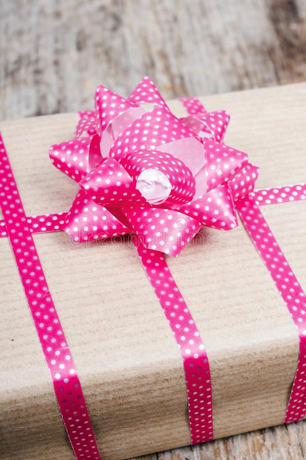 Gift with pink ribbon on wooden background royalty free stock photo