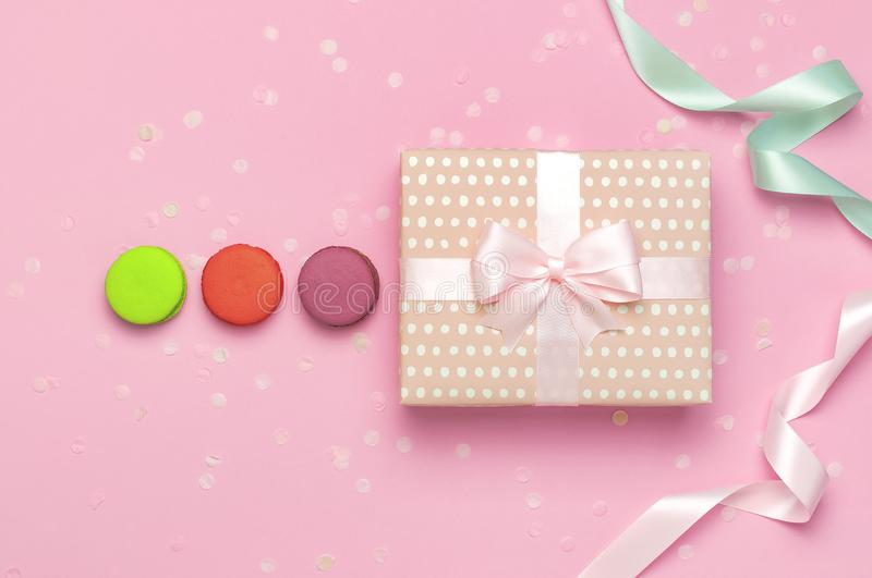 Gift or present box beautiful festive ribbon cake macaron or macaroon confetti on pink background top view. Flat lay composition stock image