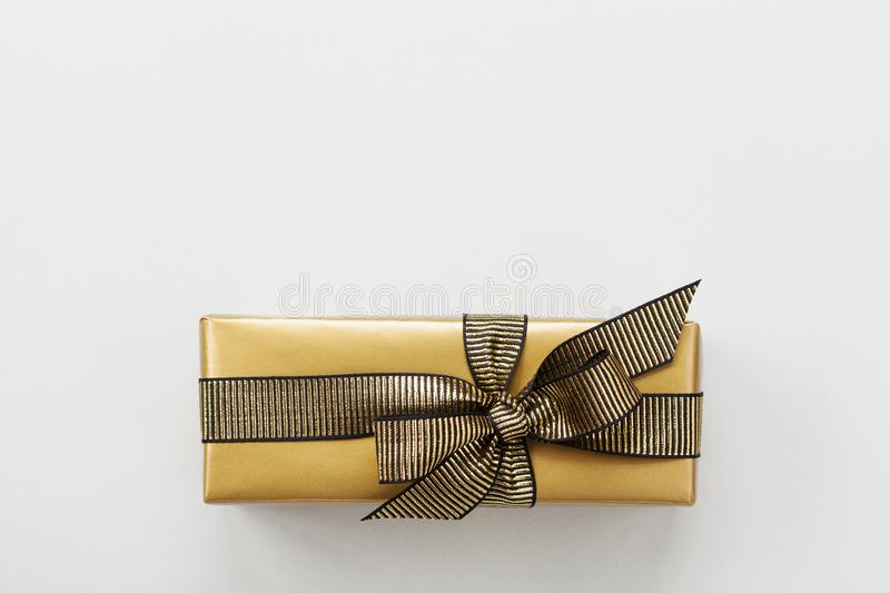 Gift or present box decorated gold ribbon on table top view. Flat lay composition for Christmas or birthday. Gift or present box decorated gold ribbon on gray royalty free stock image