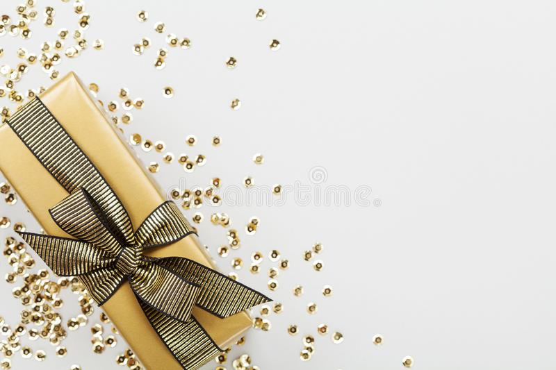 Gift or present box decorated golden sequins on table top view. Flat lay composition for Christmas or birthday. royalty free stock photos