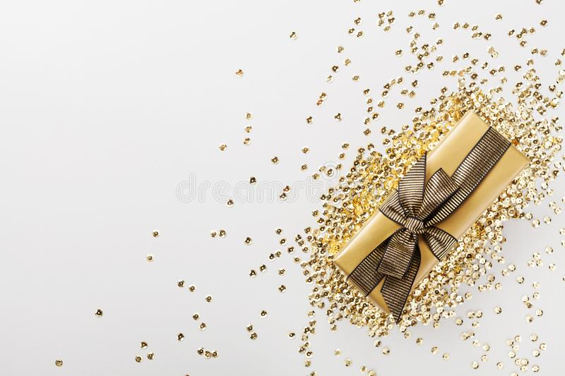 Gift or present box decorated golden sequins on table top view. Flat lay composition for Christmas or birthday. Gift or present box decorated golden sequins on royalty free stock photos