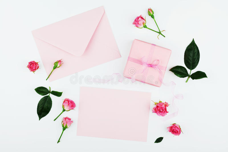 Gift or present box, envelope, paper blank and pink rose flower on white table top view in flat lay style for greeting card. Gift or present box, envelope stock photography