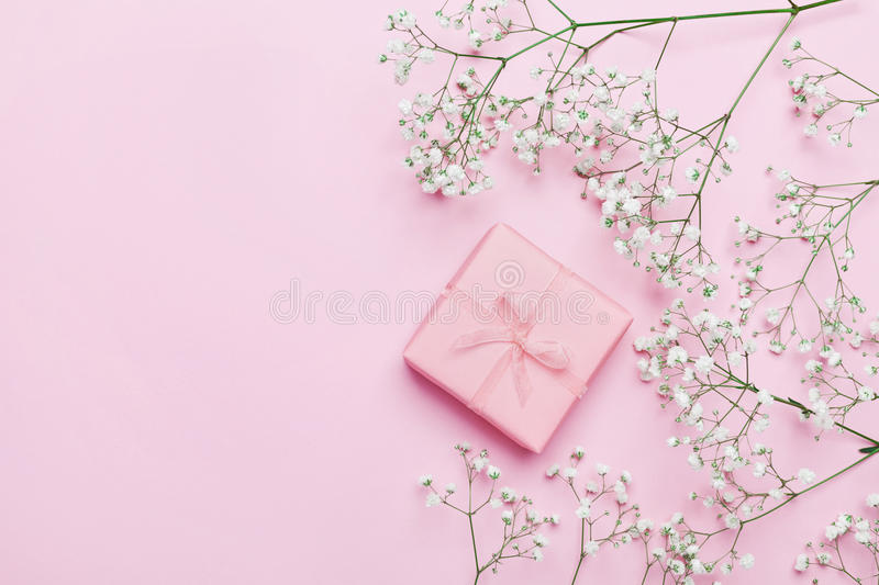 Gift or present box and flower on pink table from above. Pastel color. Greeting card. Flat lay style. royalty free stock photo