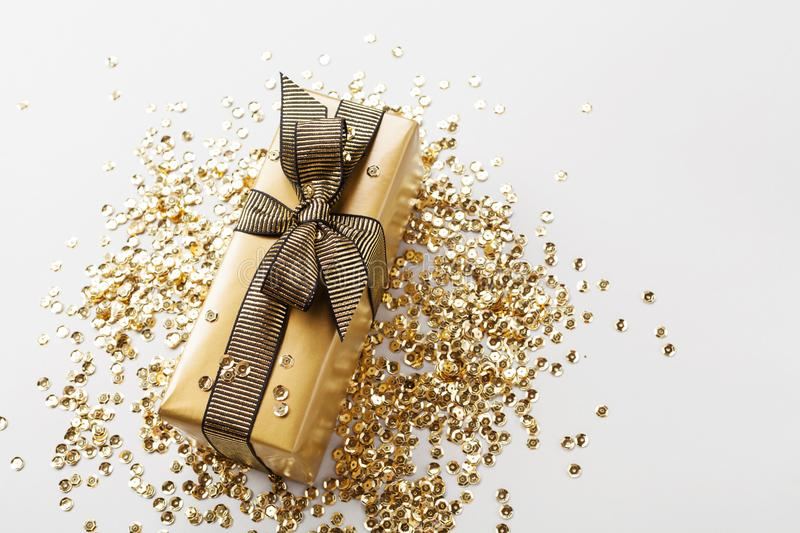 Gift or present box and golden sequins on table top view. Composition for Christmas or birthday. Gift or present box and golden sequins on gray table top view stock photo
