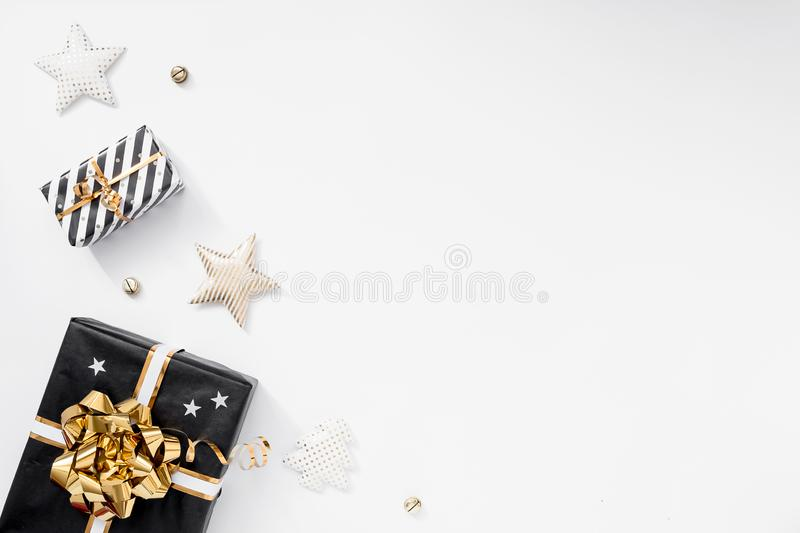 Gift or present box, party hats and stars on white table. Christmas composition with black and golden decorations royalty free stock images