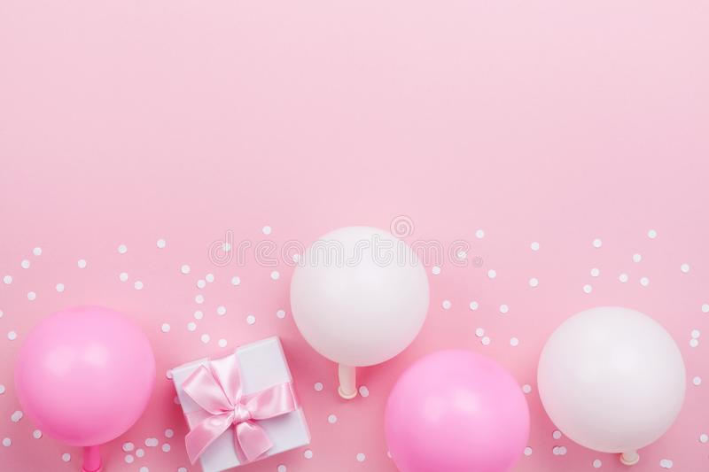 Gift or present box, pastel balloons and confetti on pink table top view. Flat lay composition for birthday, mother day or wedding. Gift or present box, pastel royalty free stock photo