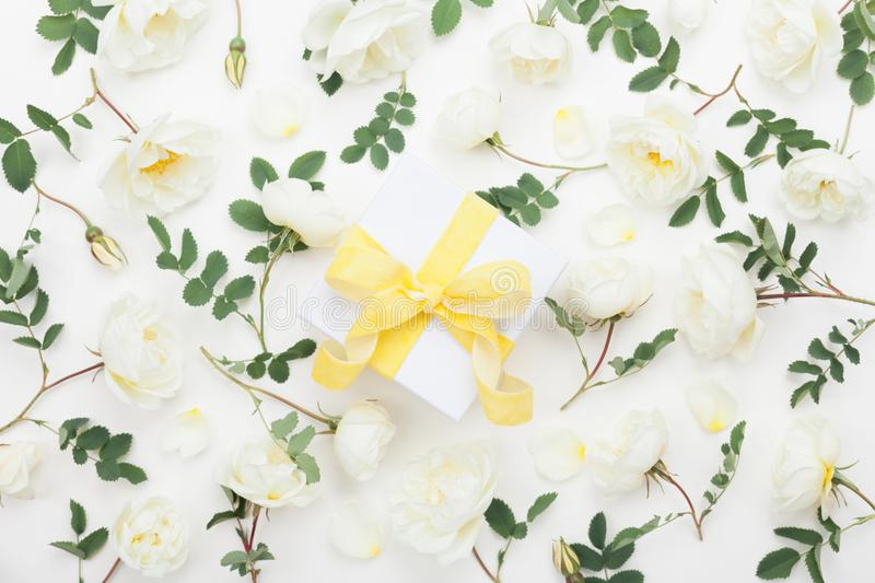 Gift or present box and pastel rose flowers decorated green leaves on white table top view. Flat lay style. stock images