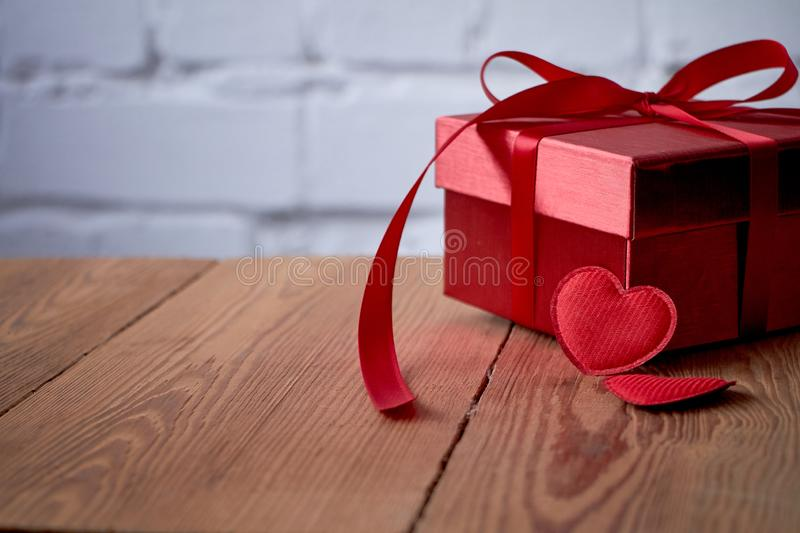 Gift or present box with red bow ribbon and glitter heart on rustic background for Valentines day. royalty free stock images
