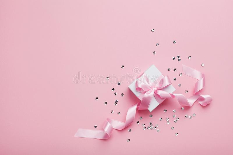 Gift or present box and sequins on pink table top view. Flat lay. Birthday, wedding or christmas concept. Gift or present box and sequins on pink table from royalty free stock photo