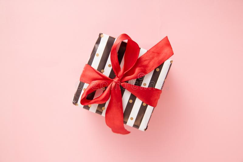 Gift or present box in white and black stripes with a red ribbon bow isolated on pink table top view. Minimal flat lay composition. For sales, birthday, mother royalty free stock photos