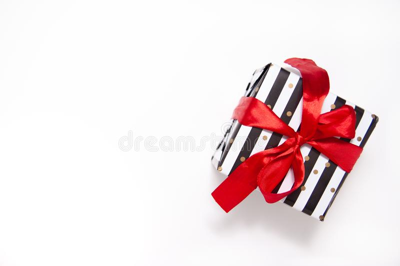 Gift or present box in white and black stripes with a red ribbon bow isolated on white table top view. Minimal flat lay. Composition for sales, birthday, mother royalty free stock photos