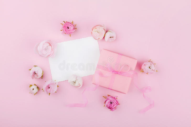 Gift or present box, white paper blank and spring flower on pink desk from above for wedding mockup or greeting card on womans day royalty free stock photos