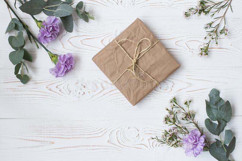 Gift or present box wrapped in kraft paper and flower on white table from above. Flat lay styling. Copy space for text. Mother day stock images
