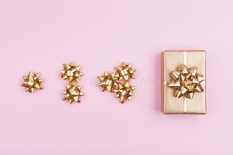 Gift or present box wrapping in golden paper with bows on pink pastel background top view. Composition for birthday, christmas. Gift or present box wrapping in royalty free stock images