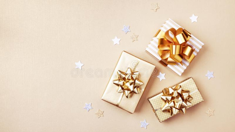 Gift or present boxes and stars confetti on golden table top view. Flat lay composition for birthday, christmas or wedding.  stock image