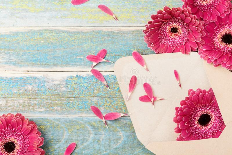 Gift or present from envelope with gerbera daisy flower. Vintage greeting background for mother or womans day. stock photo