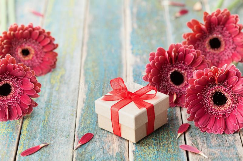 Gift or present for mother or womans day decorated with beautiful gerbera daisy flowers on vintage wooden background. Spring card. royalty free stock photography