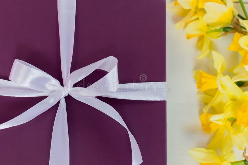 Gift, purpere doos met wit lint en gele bloemen stock foto