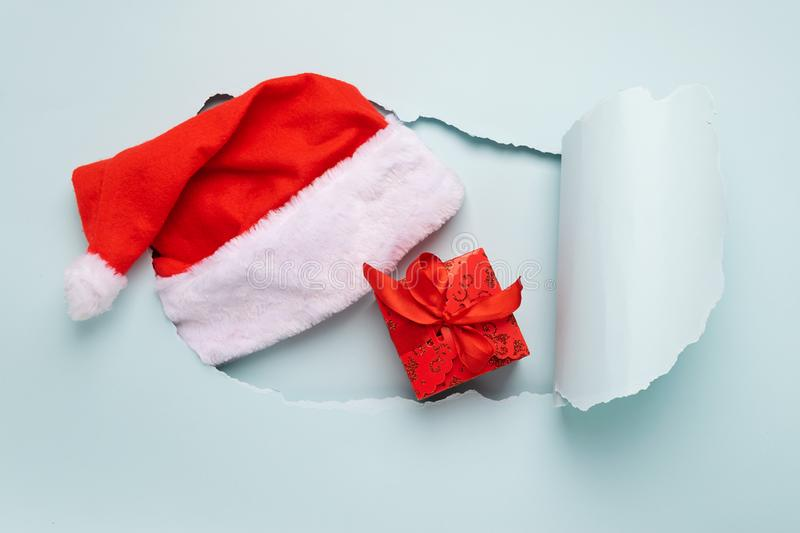 Gift with red bow cap Santa Claus big hole paper background mint color. New Year or Christmas concept. Flat layout stock photo