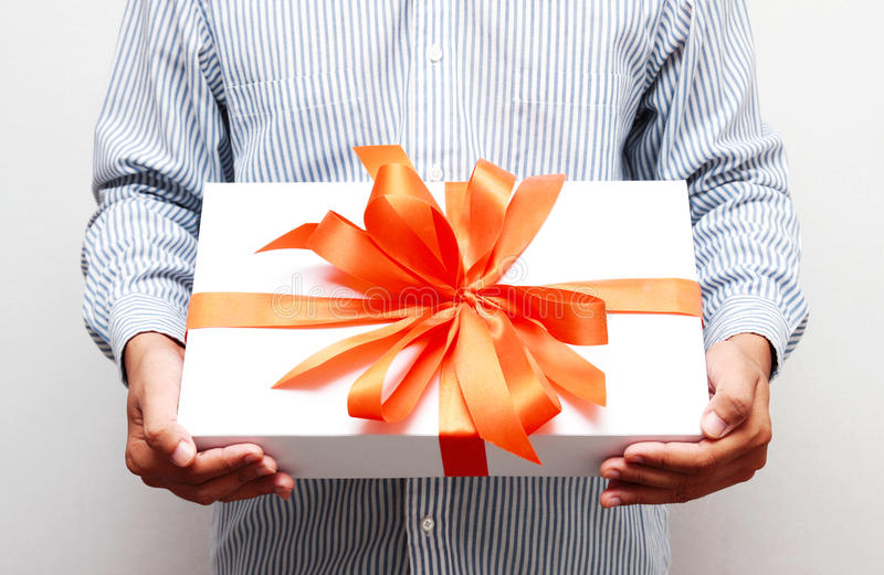 Gift with red bow in hand. The gift with red bow in hand royalty free stock photography