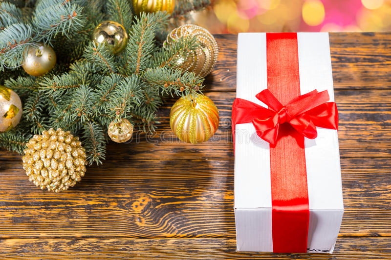 Gift with Red Bow on Table with Festive Pine Bough. High Angle Still Life of White Box Gift Wrapped in Red Bow and on Top of Table with Wood Grain and Copy Space stock photos