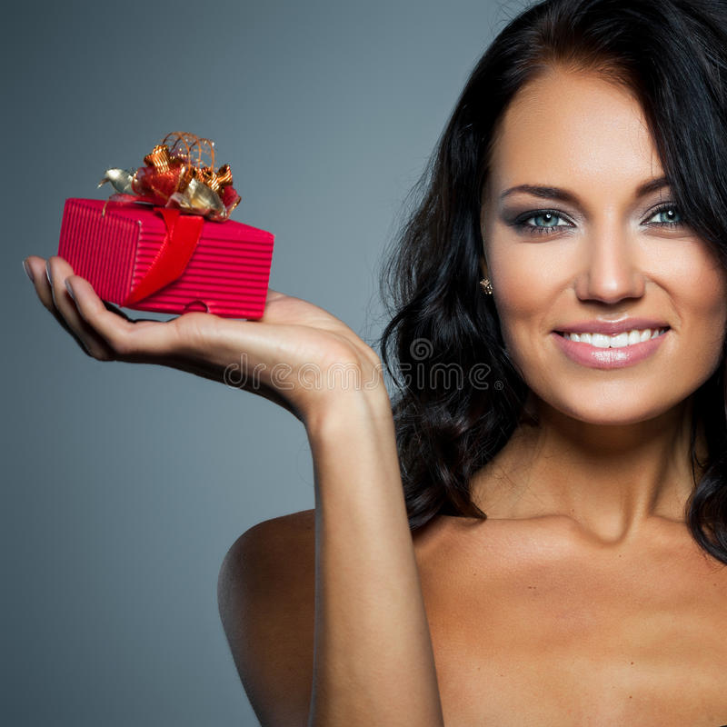 Gift in a red box. Smiling young woman holding a gift in a red box on grey background stock image