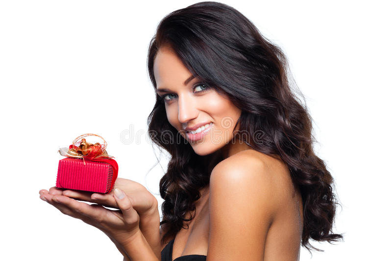 Gift in a red box. Smiling young woman holding a gift in a red box isolated on white stock images