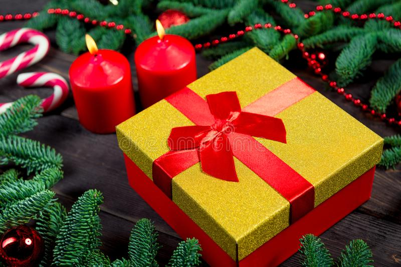 Gift with a red ribbon, burning candles and green branches of spruce on a wooden. Table royalty free stock image