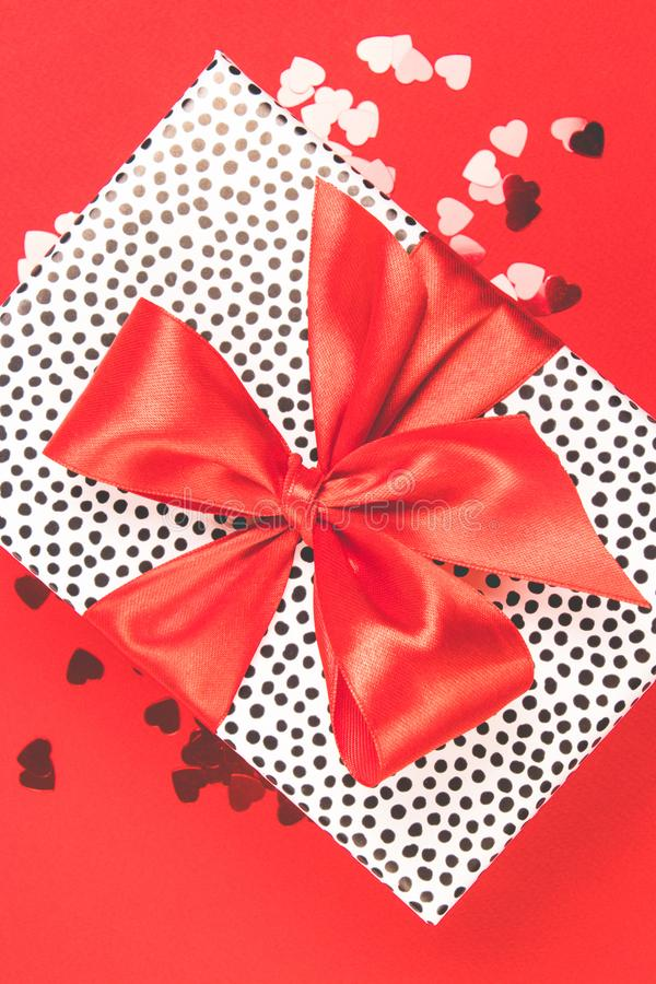 Gift with red satin bow with glitter decorative hearts on a red background. Festive concept royalty free stock photography