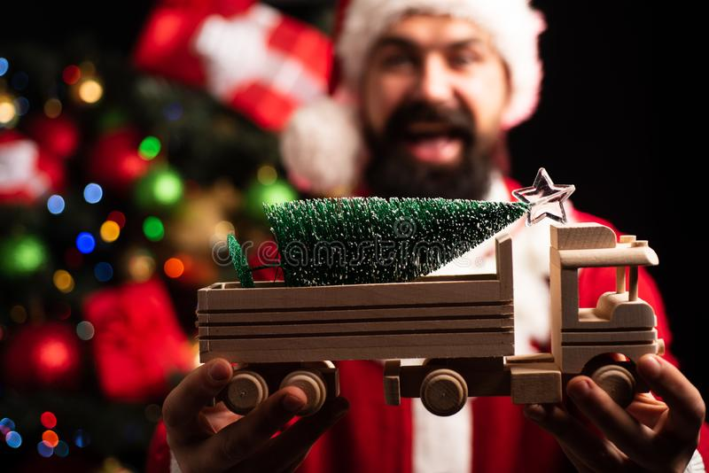 Gift from Santa. Toy wooden car for Christmas. Happy holiday for children. Childhood dream, happy childhood. Christmas. Tree Delivery. Bearded man in Santa royalty free stock images