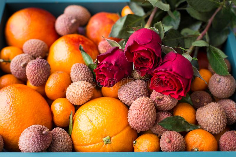 Gift set for the girl. A box of fresh fruit with red oranges, mini tangerines, lychee fruits and red roses stock photo