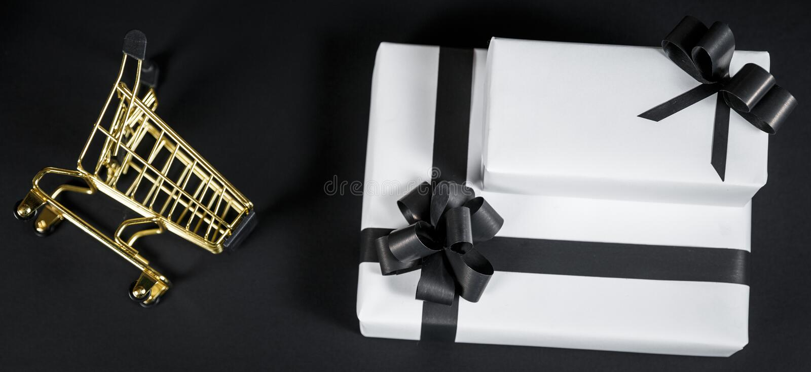 Gift in shop cart isolated on black background. stock photography