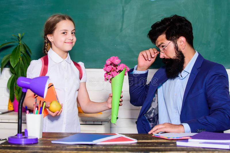 Gift. small school girl kid with flower bouquet. teachers day. Daugghter and father with flowers. flower present for stock photos