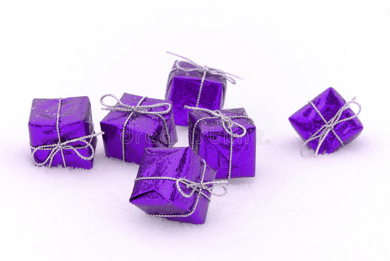 Gift in snow. Purple christmas gifts in snow in winter royalty free stock photo