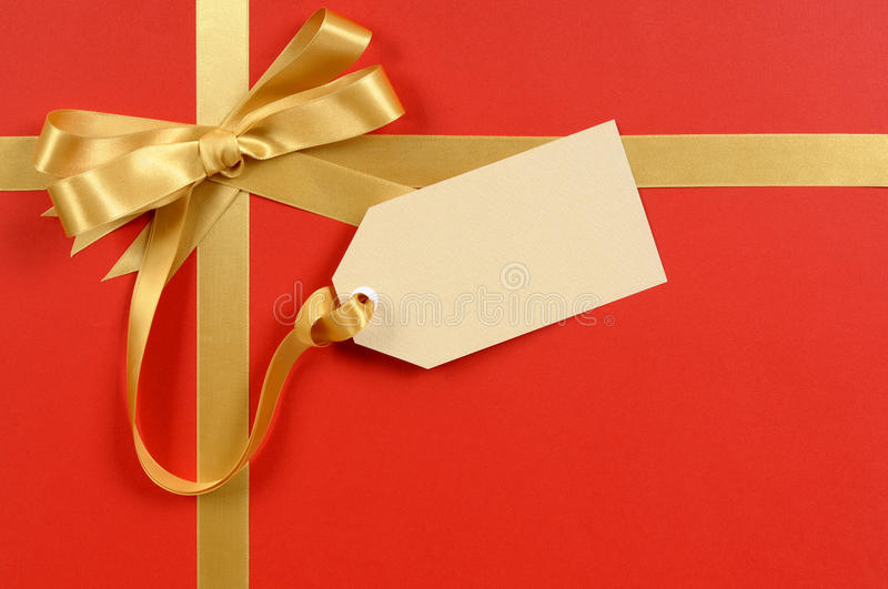 Gift tag or label, red background, gold ribbon bow, copy space, Christmas present or gift royalty free stock image