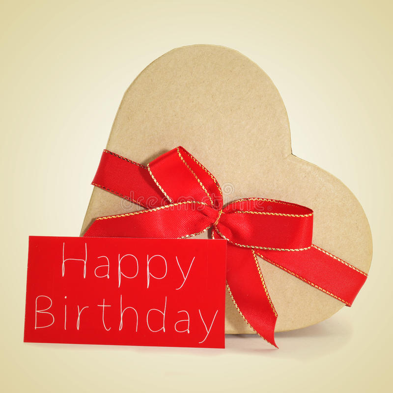 Gift and text text happy birthday in red signboard, with a retro. A heart-shaped gift and a red signboard with the text happy birthday written in it on a beige stock images