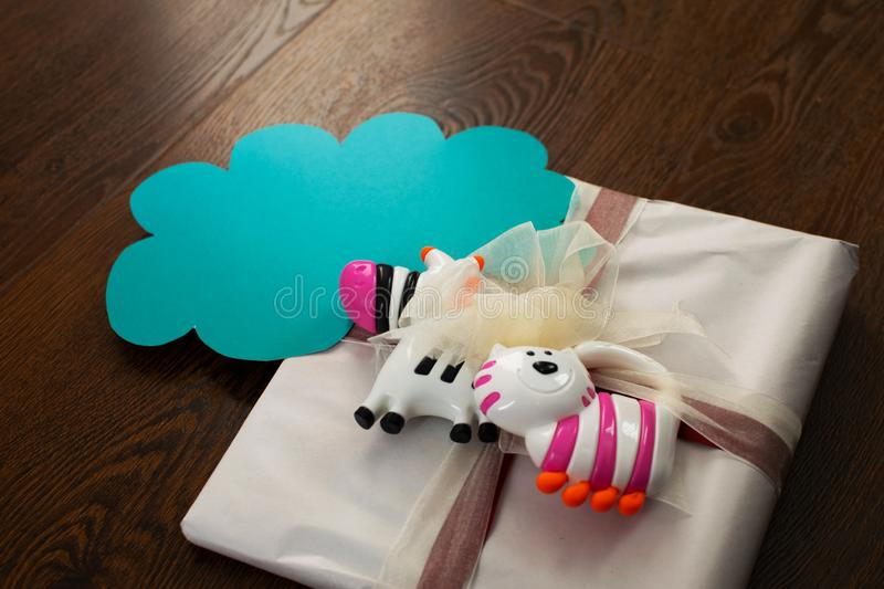 Gift tied with a bow for a newborn with rattles. Gift for newborn, birthday. Rattles for baby with paper cloud with place for text royalty free stock photo