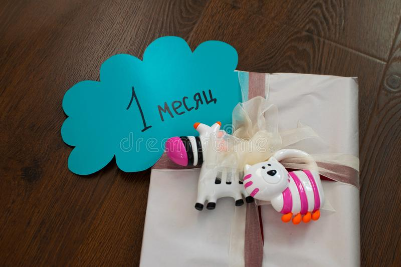 Gift tied with a bow for a newborn with rattles. Gift for newborn, birthday. Rattles for baby. Caption: 1 month. Gift tied with a bow for a newborn with rattles stock photos