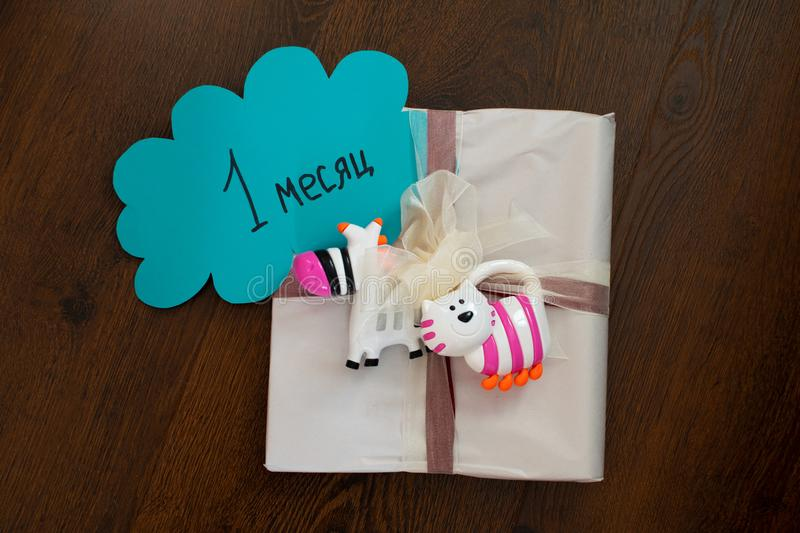 Gift tied with a bow for a newborn with rattles. Gift for newborn, birthday. Rattles for baby. Caption: 1 month. Gift tied with a bow for a newborn with rattles stock images