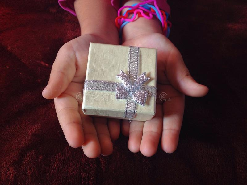 Gift to you. Gift in kids hands with dark bacground royalty free stock images
