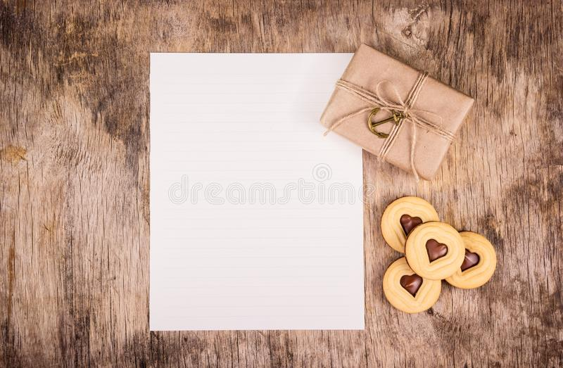 Gift for Valentine`s Day. Empty sheet of paper, gift box and chocolate hearts. Copy space royalty free stock images