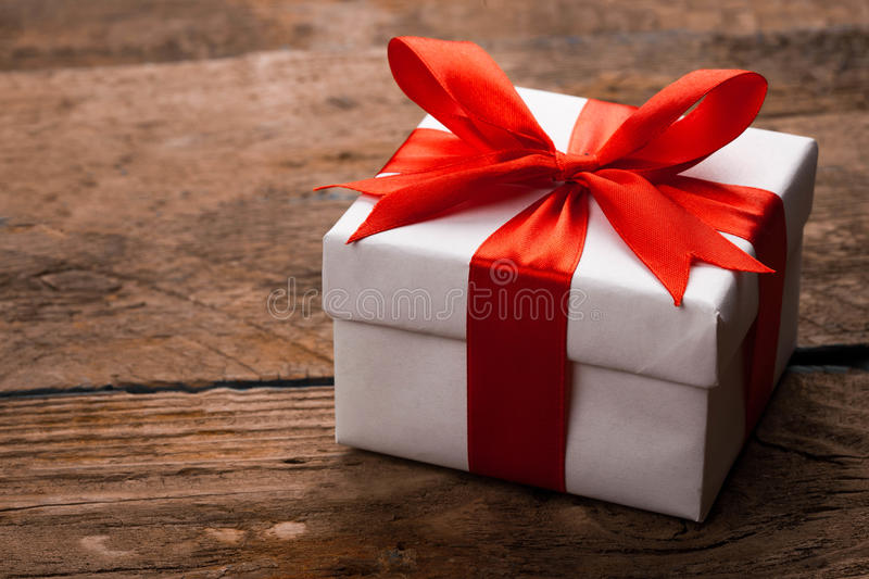 Gift on Valentine`s Day. Gift with red satin ribbon on wooden background. studio shot stock photos