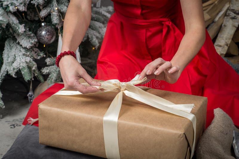 Gift voor Kerstmis: Een meisje in een rode kleding pakt een doos met een gift in en verbindt het lint stock afbeeldingen
