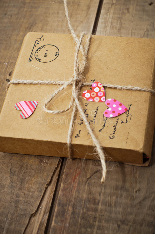 A gift on wooden background with hearts. Gift package wrapped with paper and rope with hearts on vintage wooden background stock photography
