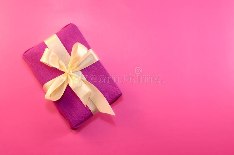 Gift wrapped and decorated with a light bow on a pink background with copy space. Flat lay, top view. copy space royalty free stock photos