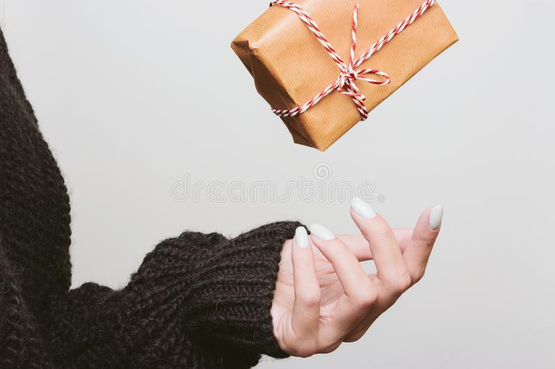 Gift wrapped falls into the hands of a girl. Gift wrapped in kraft paper falls into the hands of a girl. Toss a box royalty free stock photography